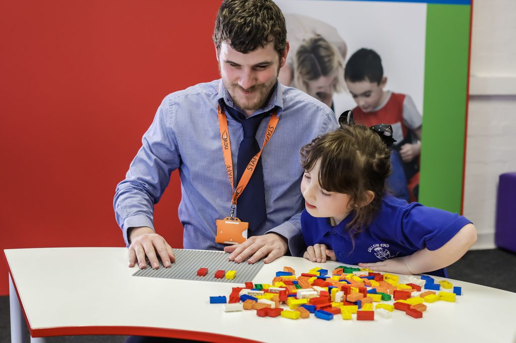 Teacher and student work with Lego's Braille bricks.