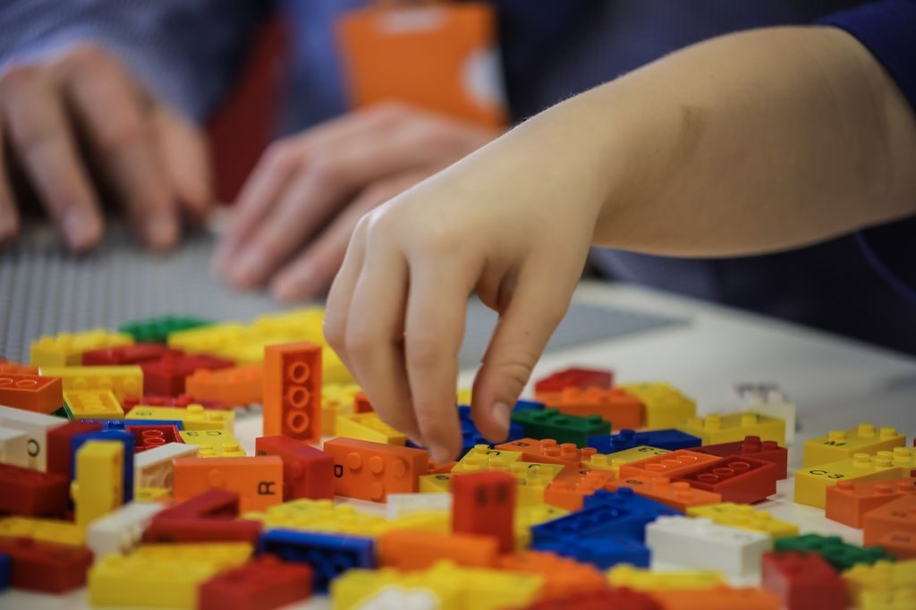 A child's hand reaches for a Braille Lego brick.