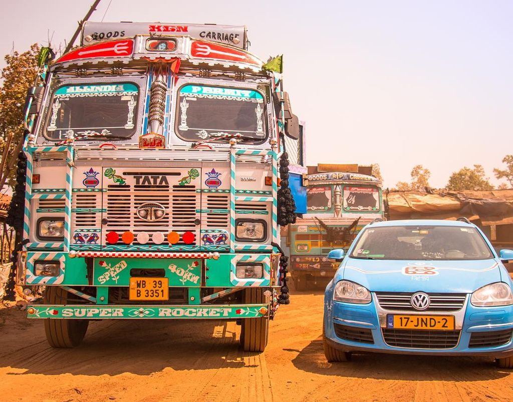 Wiebe Wakker's electric car trip, Blue Bandit next to decorated bus in India