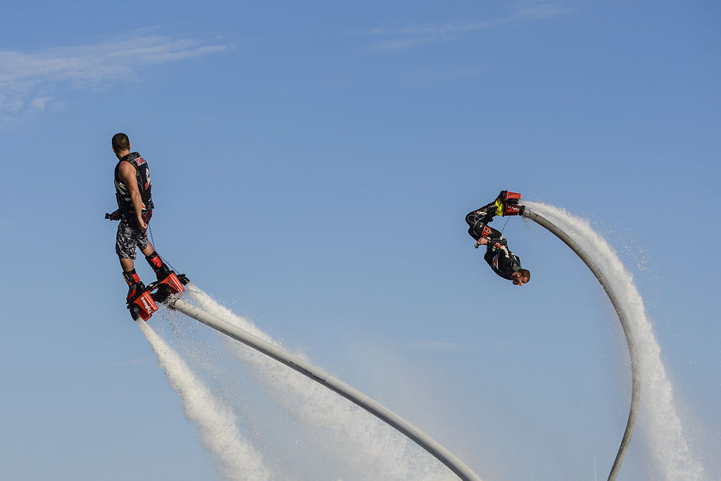 "Franky Zapata (left), inventor of the ""Flyboard"" watches as Lindsay McQueen does a backflip."