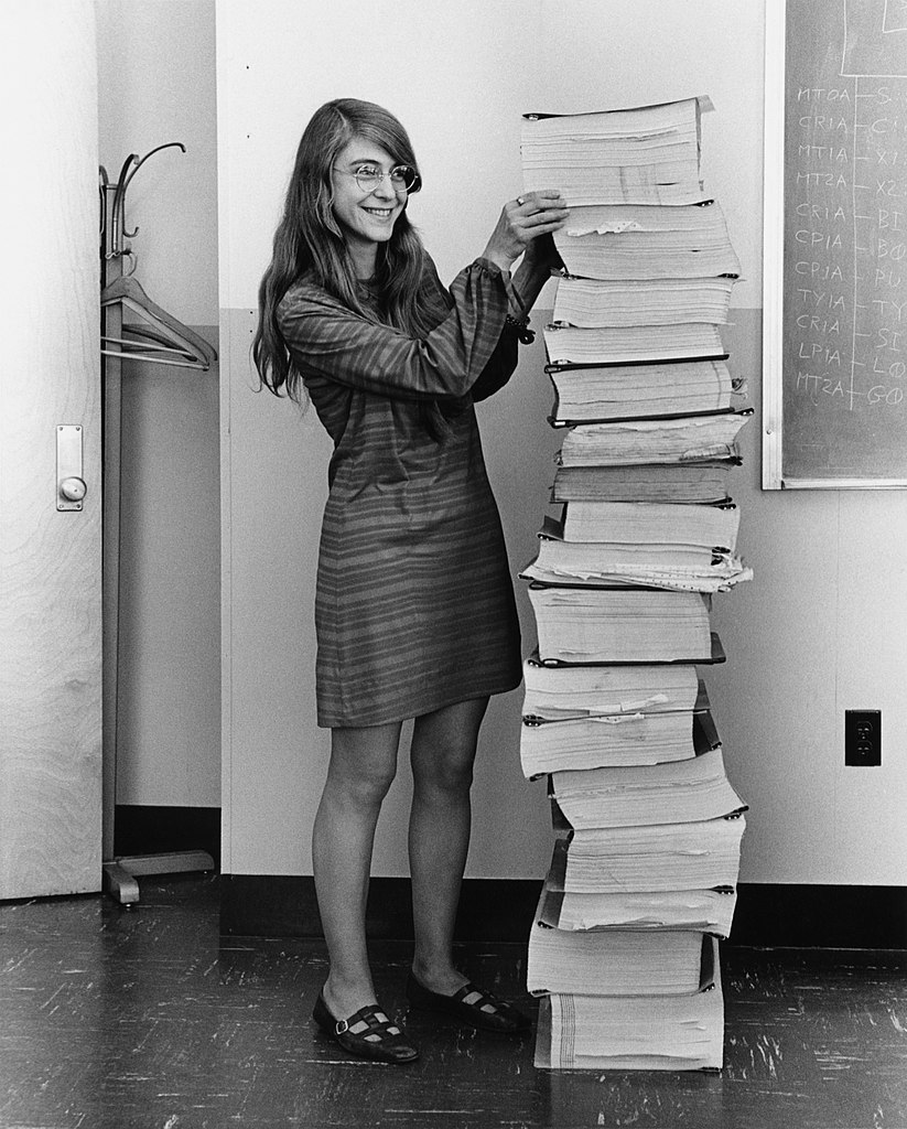Margaret Hamilton standing next to the navigation software that she and her MIT team produced for the Apollo Project.