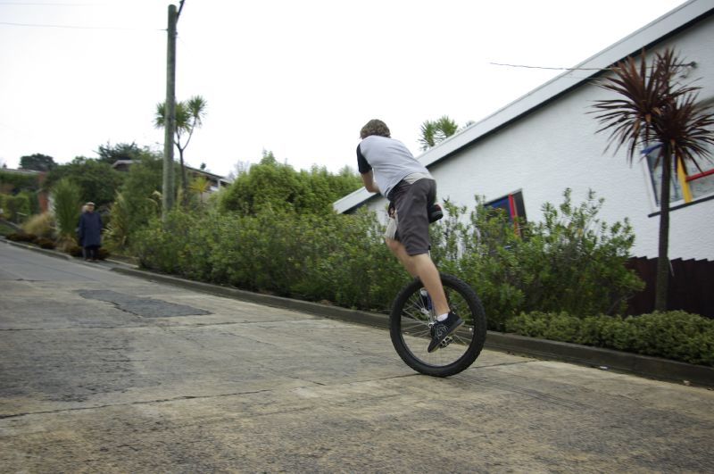 The unicyclist has to lean forward to keep his centre of gravity centred over his unicycle's contact with Baldwin Street, on the steeper cement covered portion of the street.