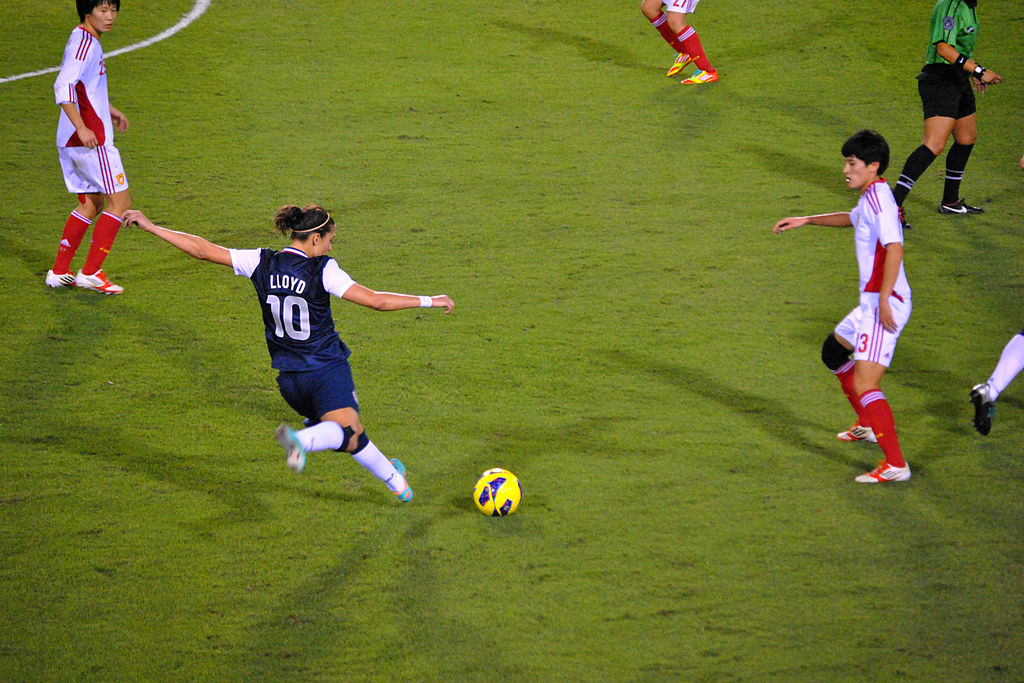 Carli Lloyd about to kick a soccer ball.