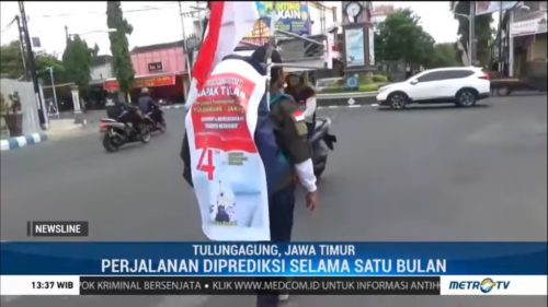Medi Bastoni is shown walking backward through traffic in a screenshot from an Indonesian TV news program.