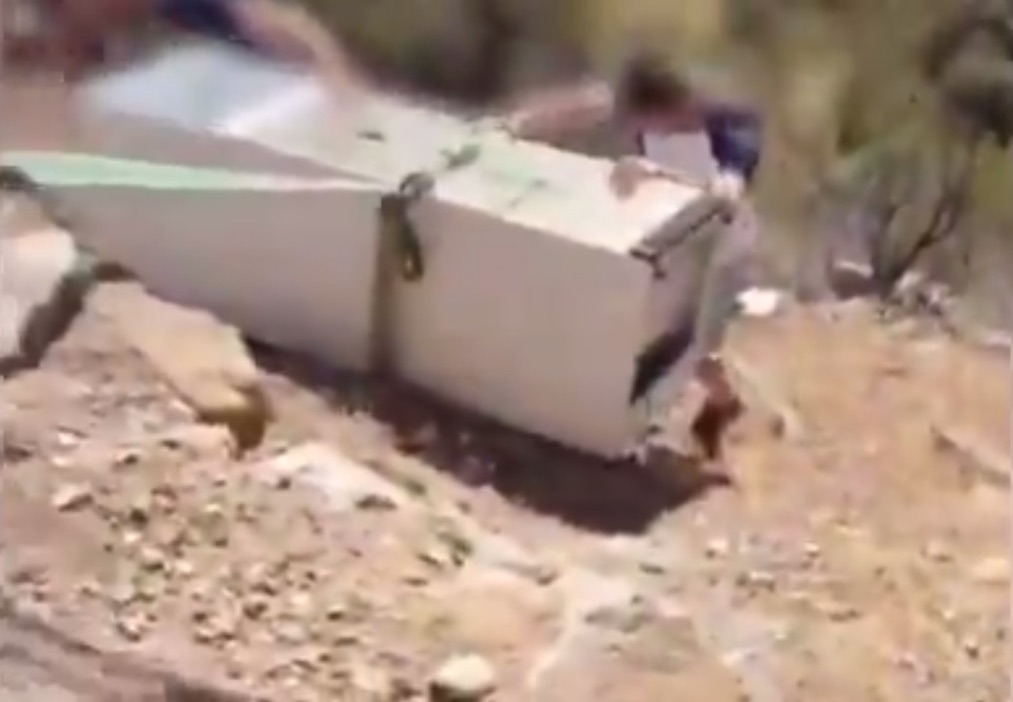 A man works to get a refrigerator back up a hill.