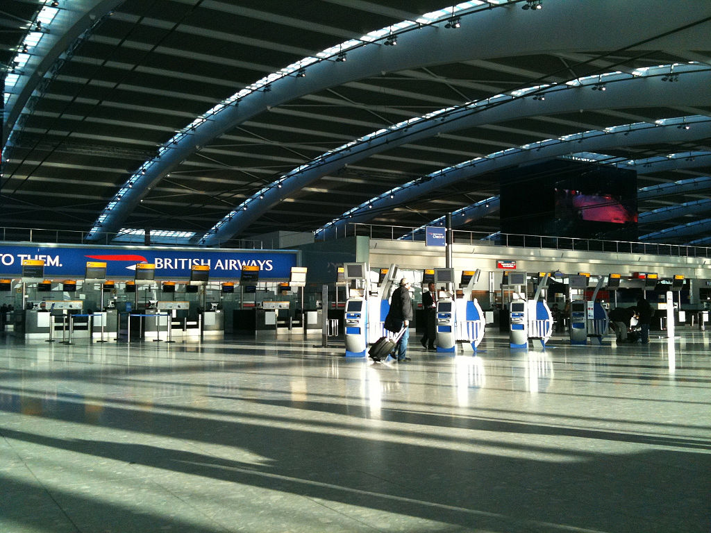 Nearly empty Heathrow Terminal 5 in 2010, with one woman walking, BA check-in counters in the background