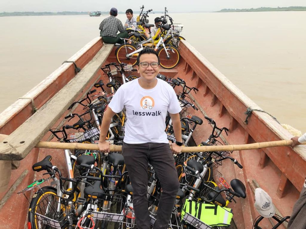 Mike Than Tun Win in front of wooden boat full of bikes.
