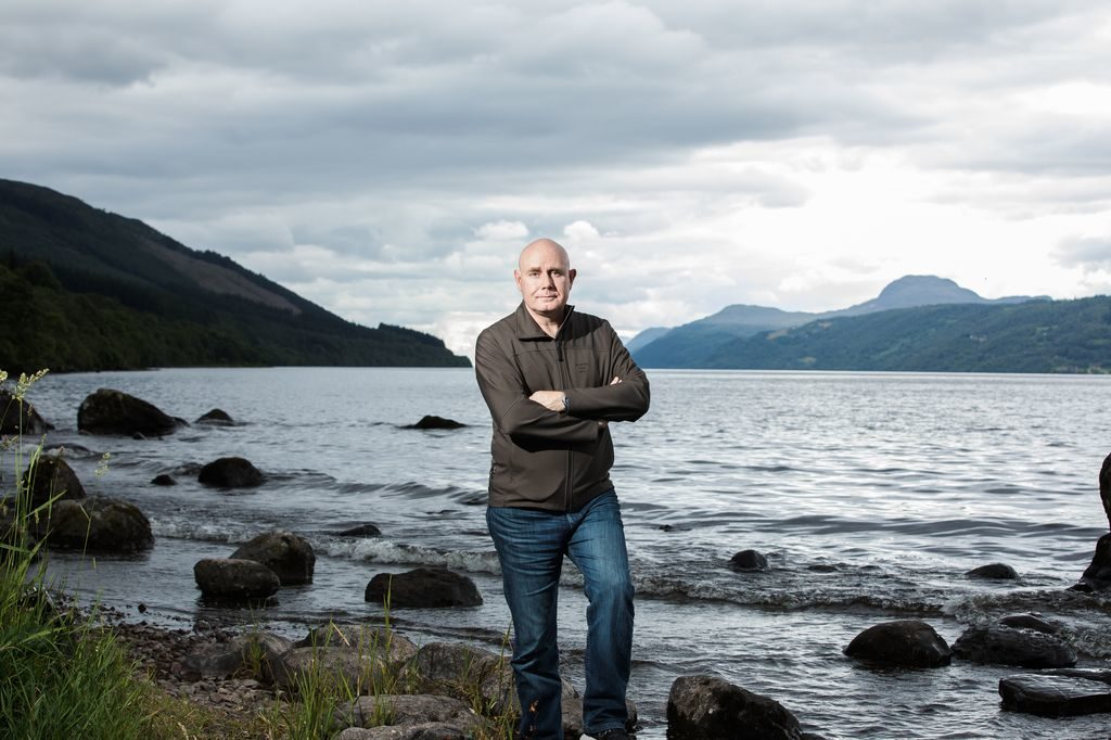 Portrait of professor Neil Gemmell beside Loch Ness, as seen on Beneath The Waves: Solving The Mystery of Loch Ness.
