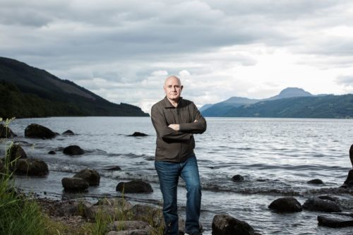 Portrait of professor Neil Gemmell beside Loch Ness, as seen on Beneath The Waves: Solving The Mystery of Loch Ness.