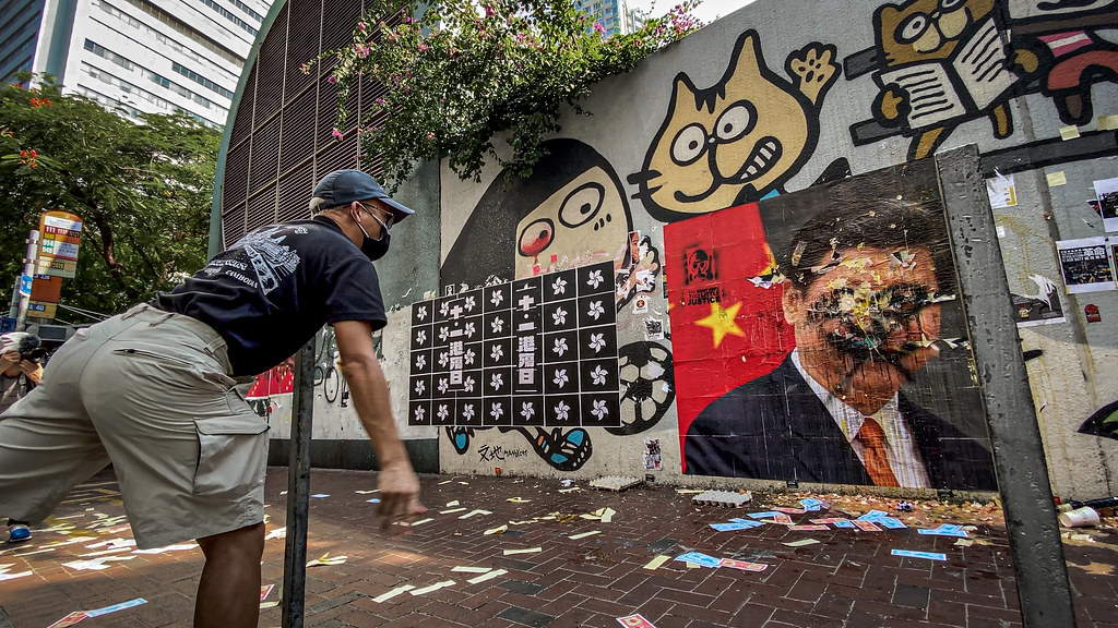 Hong Kong protester throws something at a defaced painting of Chinese President Xi Jinping.