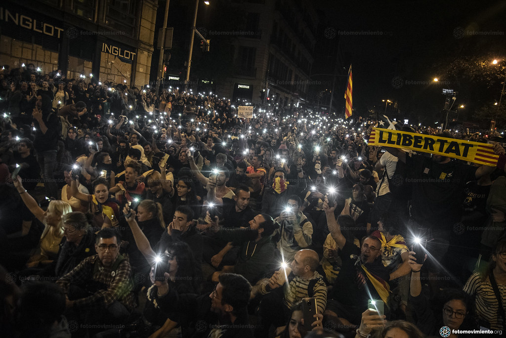 Protesters seated quietly at night with phone flashlights raised.