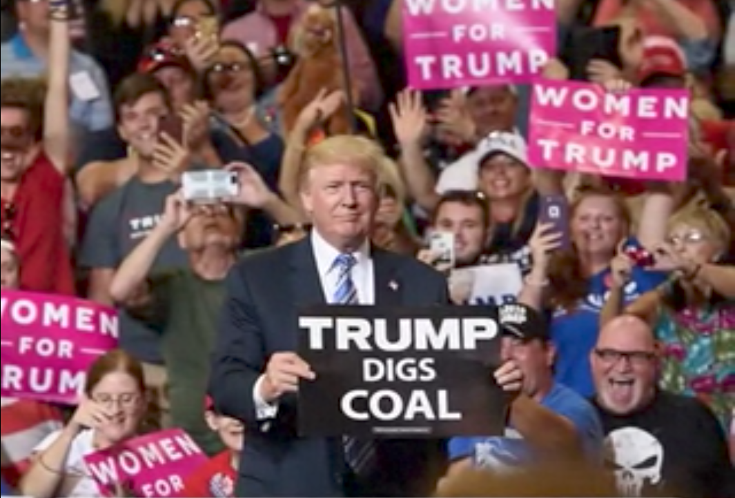 Donald Trump holding a 'Trump Digs Coal' sign at a rally in Harrisburg
