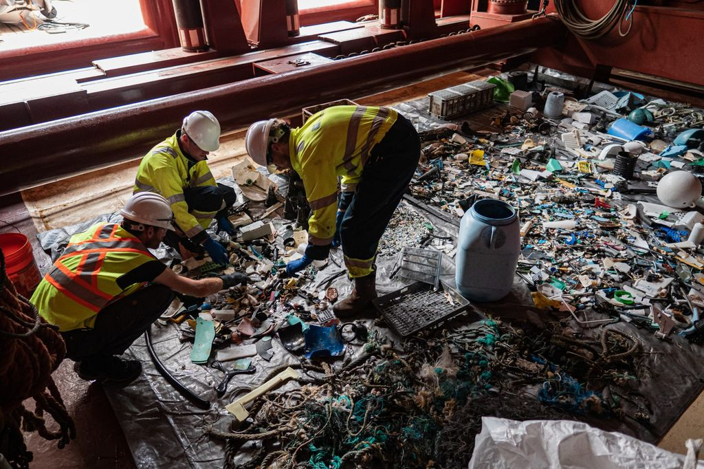 Workers sort through plastic collected by the Ocean Cleanup's System 001/B