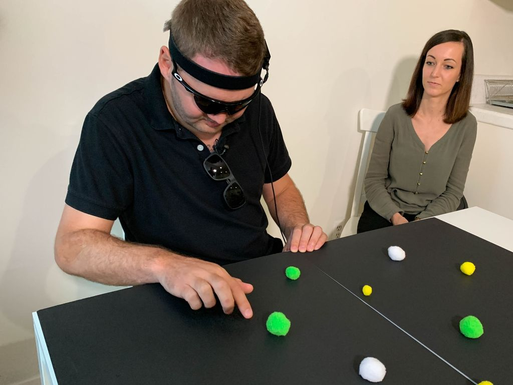 Jason Esterhuizen, who lost his vision in a car accident, practices finding objects with his wife, Sumarie. A video camera on his glasses signals an experimental device in his brain, enabling him to distinguish light from dark.