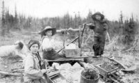 Three children operating rocker at a gold mine on Dominion Creek, Yukon Territory, ca. 1898