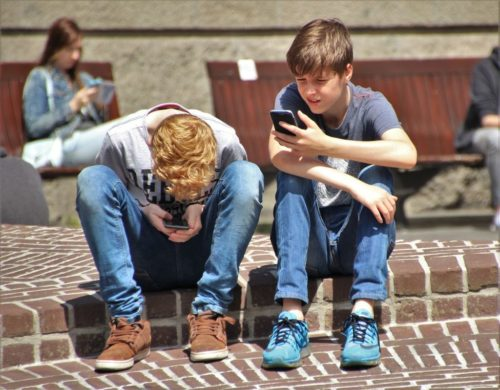 Two Boys Using Their Smartphones outside.