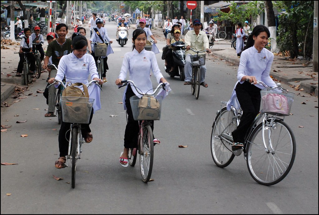 Schoolgirls on bikes on their way to school in Vietnam.