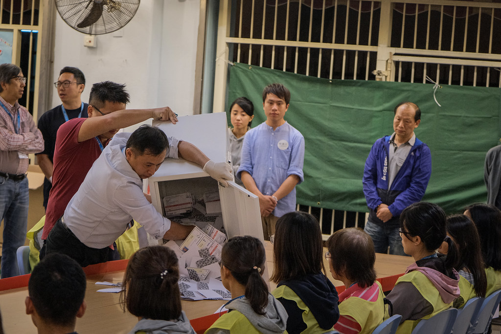 Worker dumping ballots out of a ballot box for counting in Hong Kong.