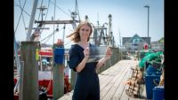 Lucy Hughes poses on a dock with a sheet of MarinaTex.