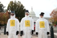 Three activists in white hazmat suits with cell phones strapped to their heads scan people in Washington, DC.
