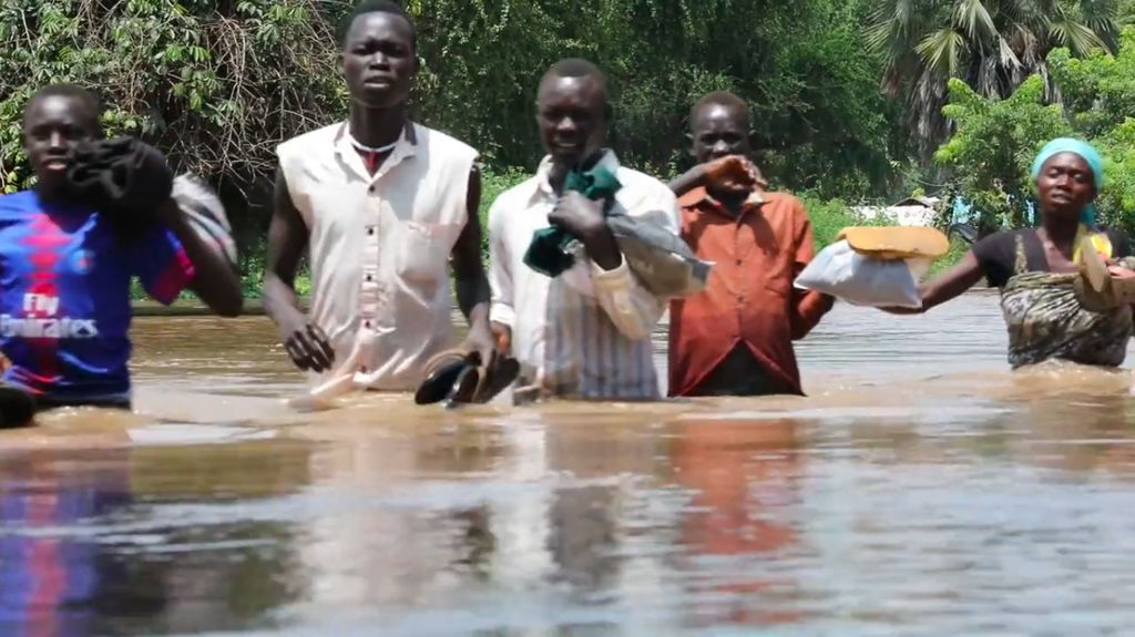 People walk through waist deep floodwaters in South Sudan.