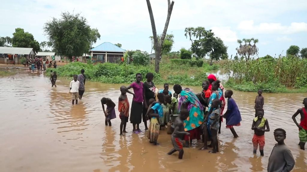 View of women and children at flooded water pump in flooded South Sudan village.
