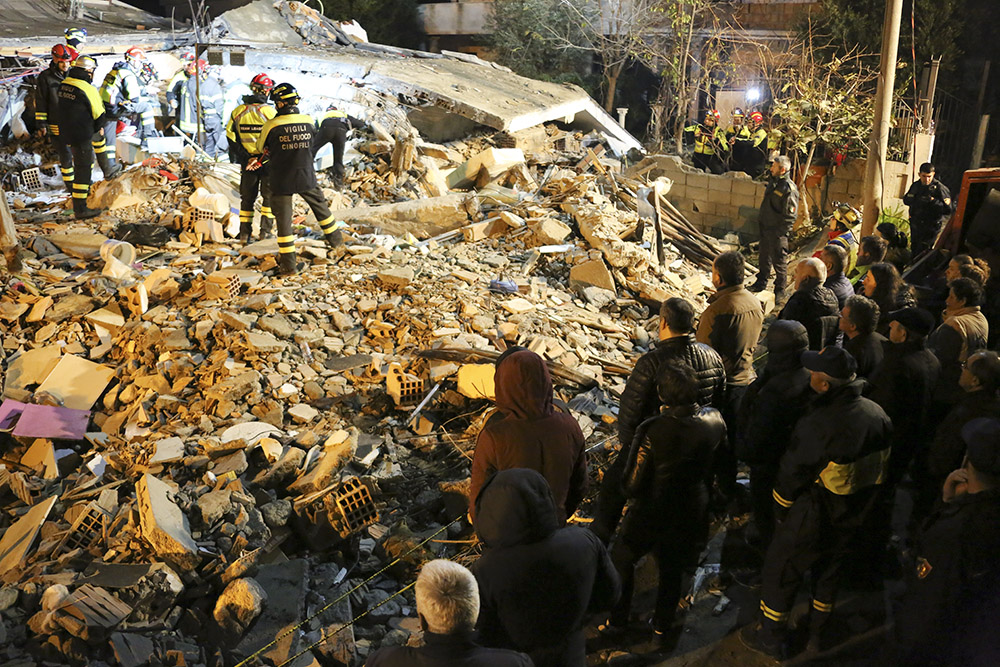 A crowd looks on as rescuers sort through rubble after the earthquake in Albania.