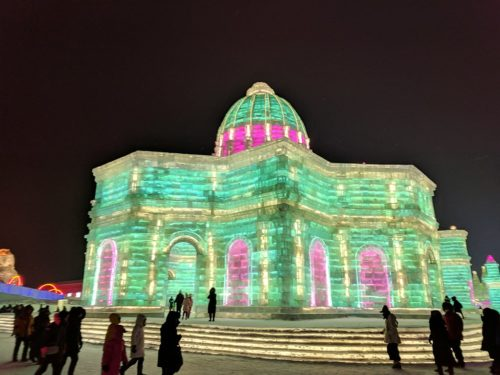 Large, domed building made of ice, lit with green and pink light, at the Harbin Ice and Snow Sculpture Festival, 2018