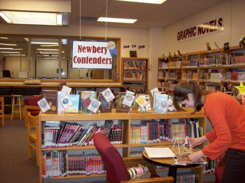 Librarian shelving under a sign saying Newbery Medal Contenders.