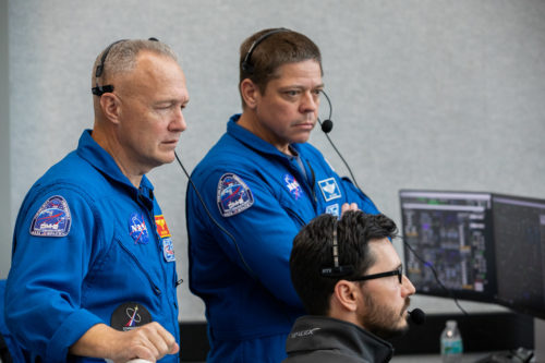 NASA astronauts Doug Hurley, left, and Bob Behnken watch the liftoff of a SpaceX Falcon 9 rocket and Crew Dragon spacecraft on the uncrewed In-Flight Abort Test, Jan. 19, 2020