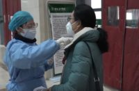 A nurse measuring the body temperature for outpatients in Hubei TCM Hospital