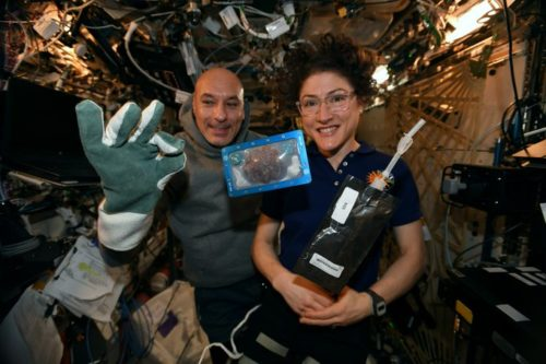 Astronauts Luca Parmitano and Christina Koch pose in the International Space Station with the first cookies baked in space. Ms. Koch joked that they had baked cookies and milk for Santa.