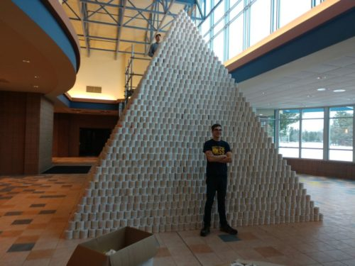 Maxton Herst, captain of the BlitzCreek 3770 Robotics team stands in front of the toilet paper pyramid.