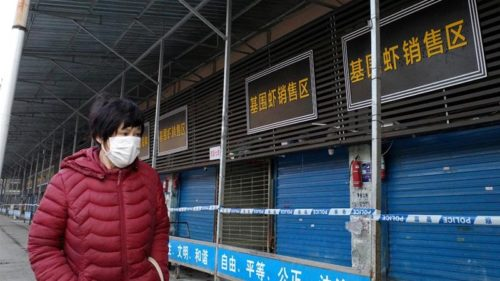 A pedestrian in a face mask walks past the Huanan Seafood Wholesale Market market in Wuhan, which was closed after a novel coronavirus was determined to originate there.