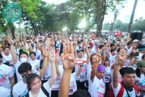 Runners raise their fingers in a three-finger salute at the Run Against Dictatorship in Bangkok.