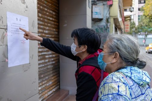 Street photo in Guangzhou - two people wearing face masks looking at a notice, presumably about the coronavirus.