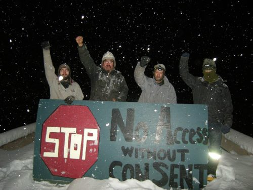 "Unist'ot'en Camp members holding a large sign reading ""No access without consent"""