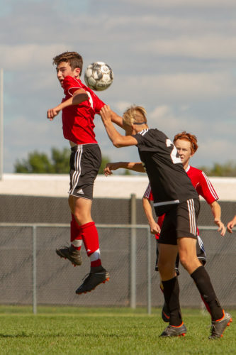 Boys in air struggling to head soccer ball.