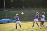 Girl heads soccer ball toward other players.