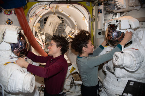 NASA astronauts Christina Koch (left) and Jessica Meir work on their U.S. spacesuits ahead of a spacewalk they conducted to install new lithium-ion batteries (Jan. 15, 2020)