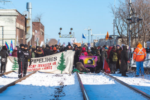 group of protestors looking east with sun good light - Wet'suwet'en Solidarity Event - Toronto Train Stopped at Dufferin Street and Bartlett Avenue in Toronto - Saturday, February 8, 2020