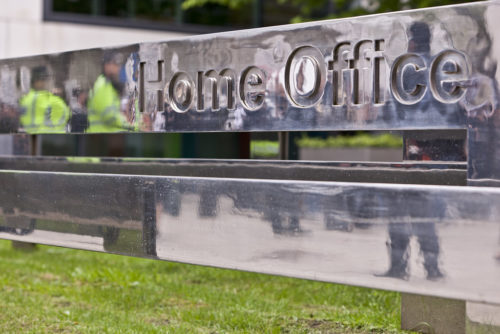 Home office sign with police reflected.