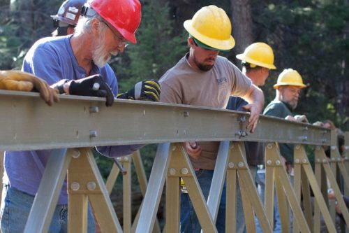 Local trail loving volunteers assemble and put into place a foot bridge across Pine Creek as part of the Bearfoot Trail project in Pine, AZ.