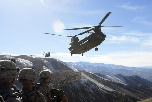 Soldiers with the 101st Division Special Troops Battalion, 101st Airborne Division watch as two Chinook helicopters fly in