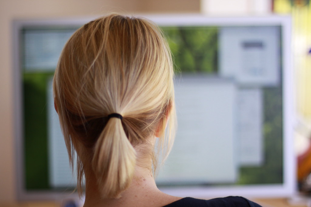 View of a woman from behind as she works on a computer.