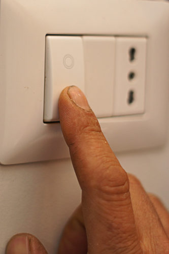 Finger turning off a switch.