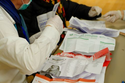 Election workers wearing masks and gloves count ballots after city elections in France on March 15, 2020. (2020-03-15 19-07-02 election-Belfort)