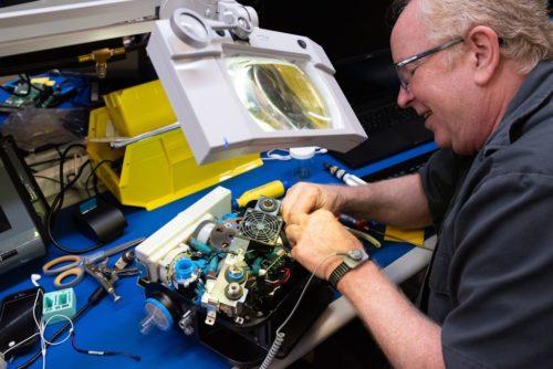 A technician works on a ventilator.