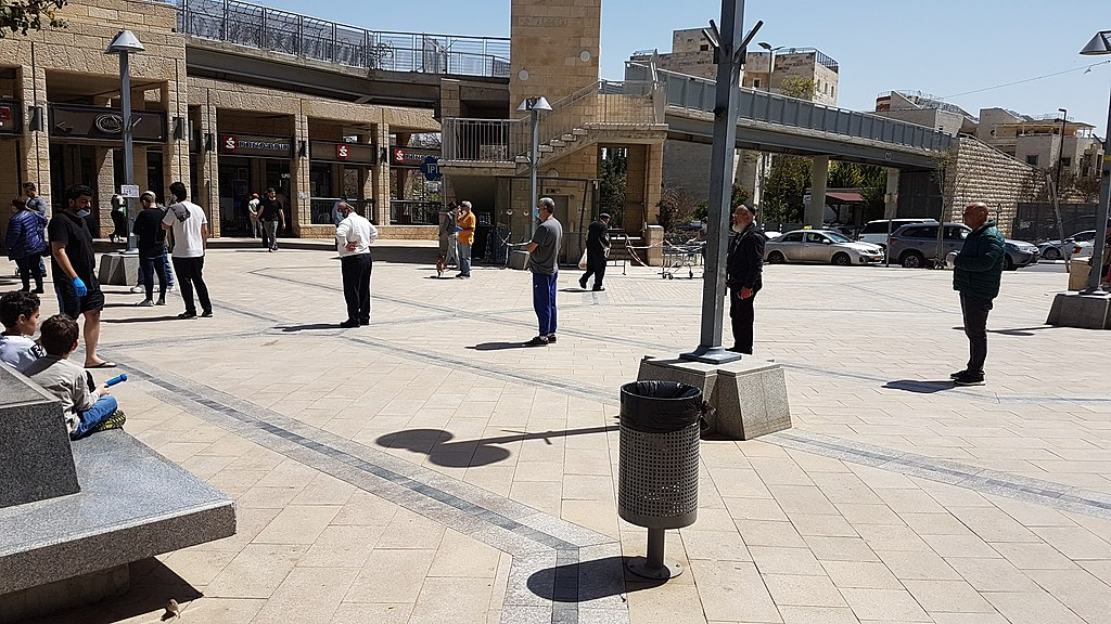 A queue of people applying physical social distancing outside of a supermarket in Jerusalem