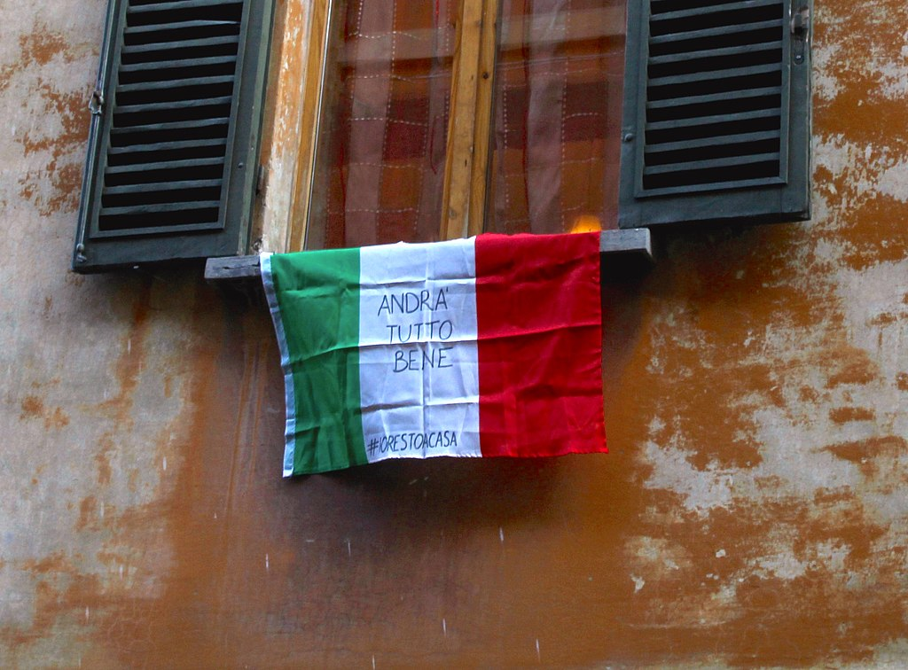 """An Italian flag hung outside of a window in Bologna with the slogan """"Andrà tutto bene"""" (Everything is gonna be fine) during the Covid-19 pandemic in 2020. (#iorestoacasa: #istayathome)"""